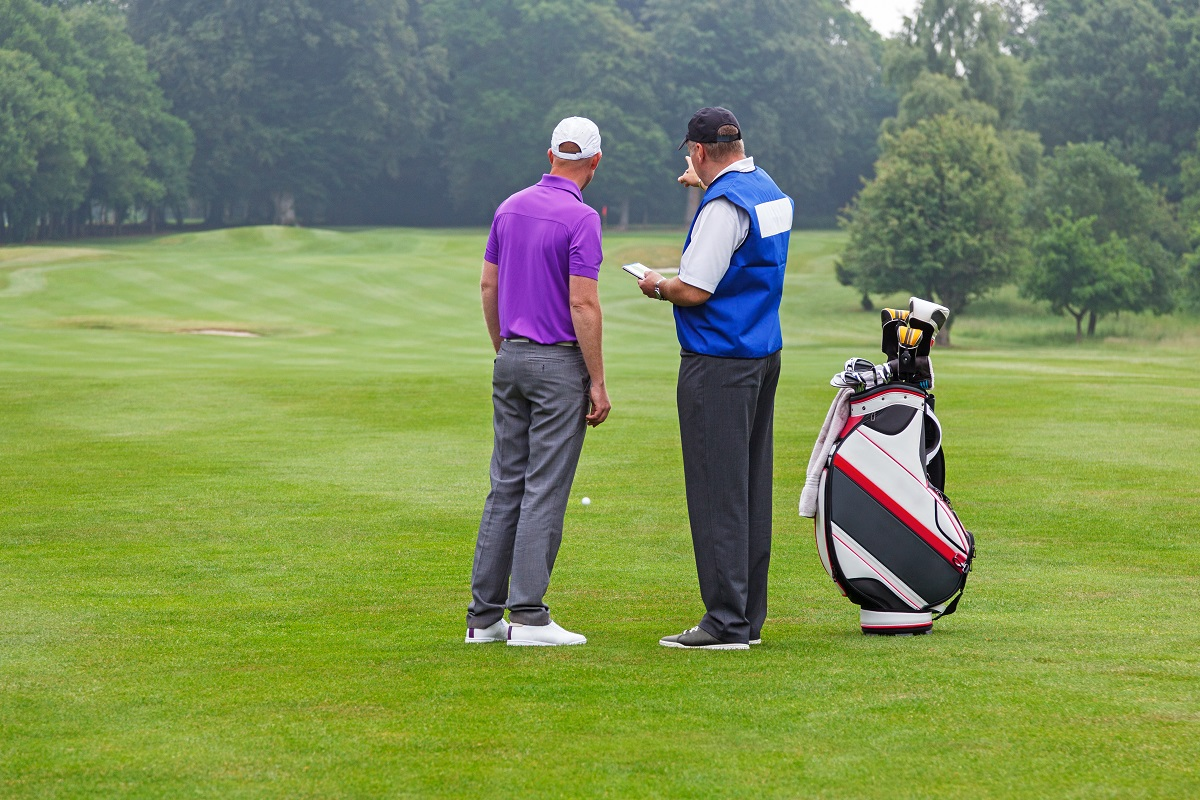 A golfer and a caddie discussing strategy.
