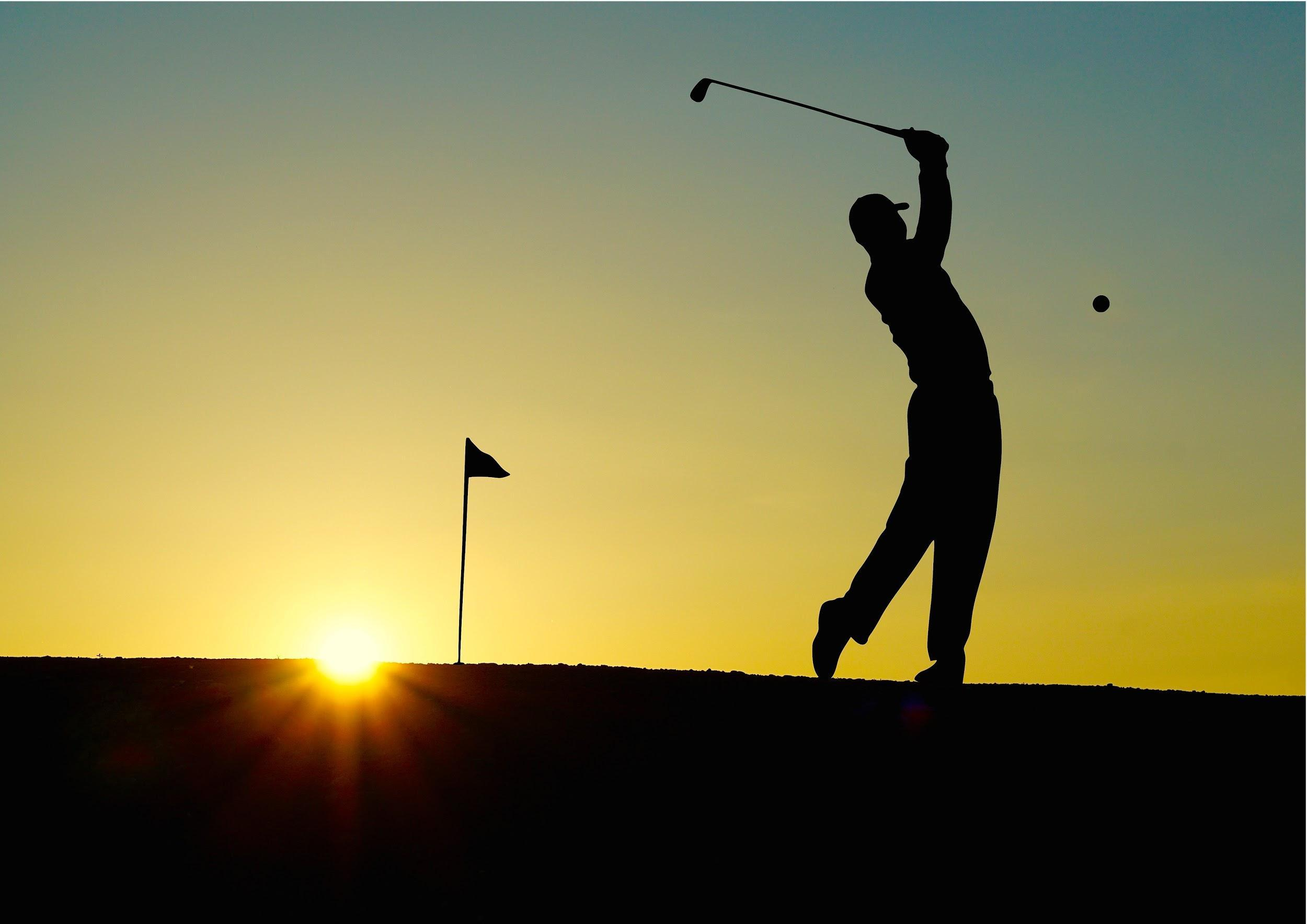 golfer playing golf during beautiful sunset