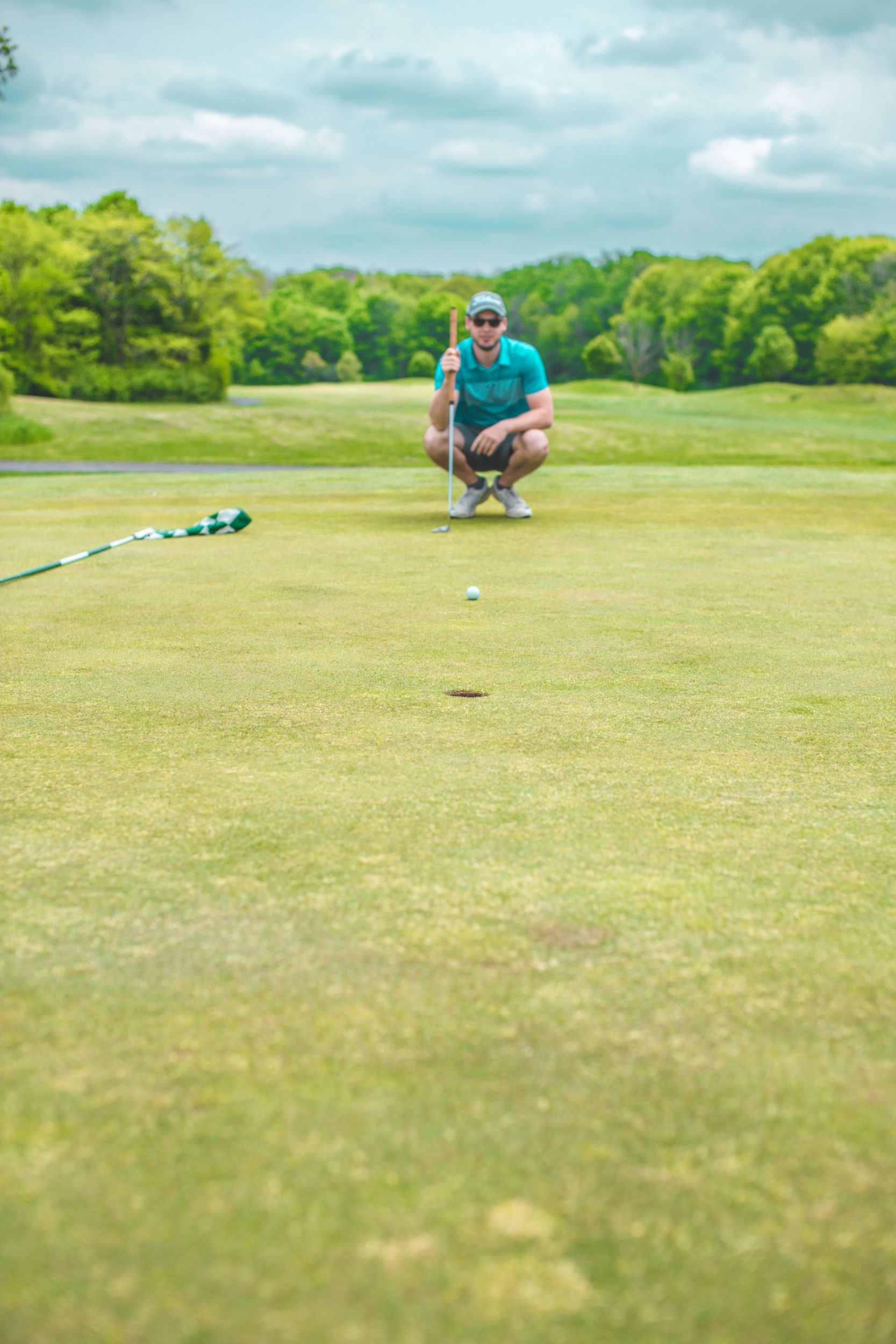 A golfer reading greens to get ready for a putt