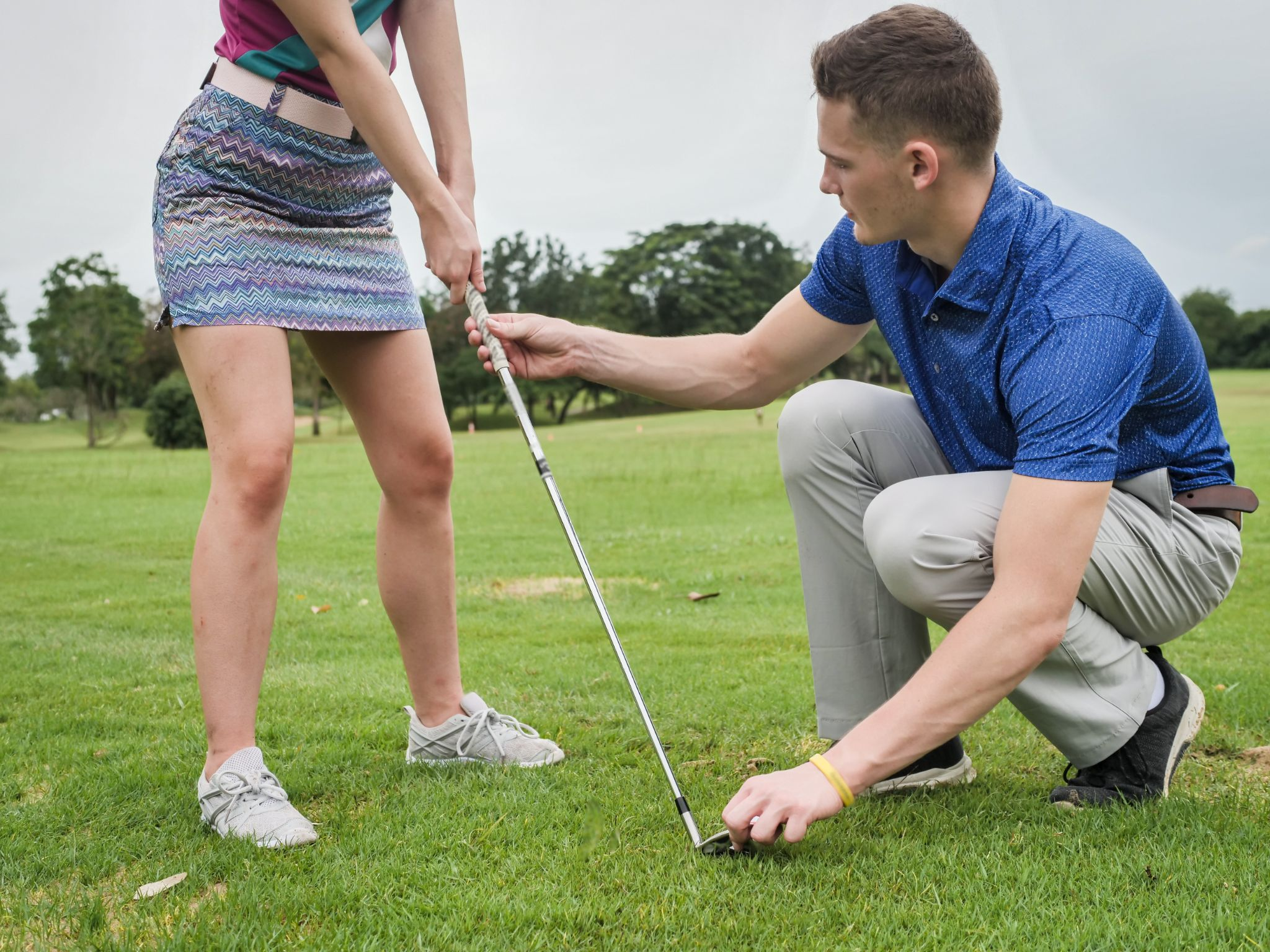 Golfer teaching his girlfriend how to play golf