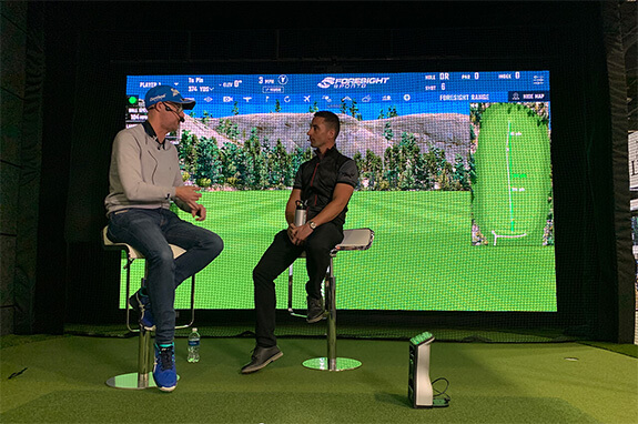 Two spokespersons talking on stage at the Foresight Sports booth at the 2020 PGA Merchandise Show in Orlanda, Florida.