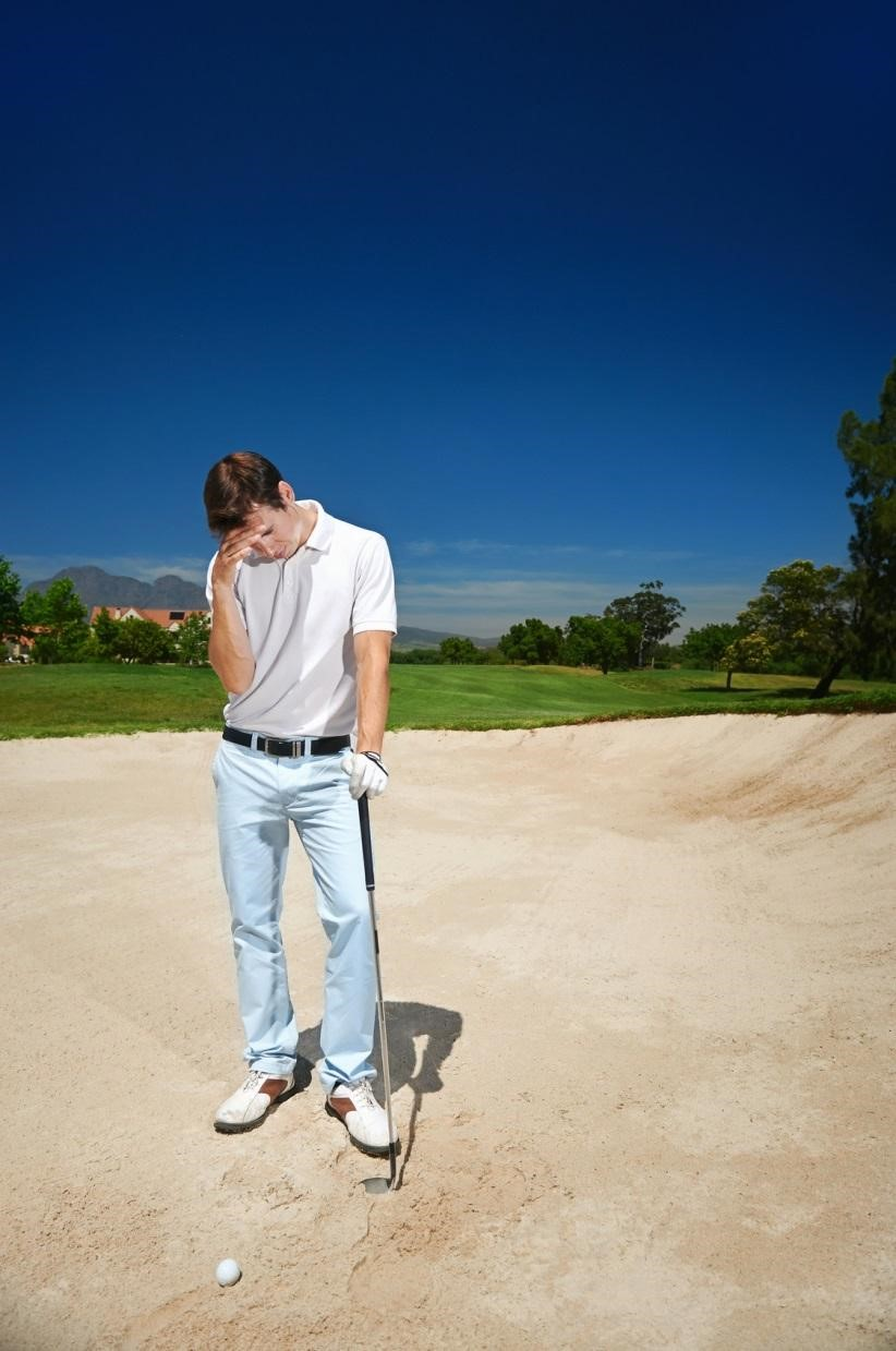 sad golfer standing in the bunker