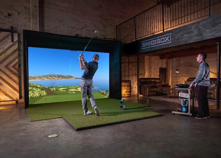 A golfer practicing with Foresight Sports SIM-IN-A-BOX™ setup.