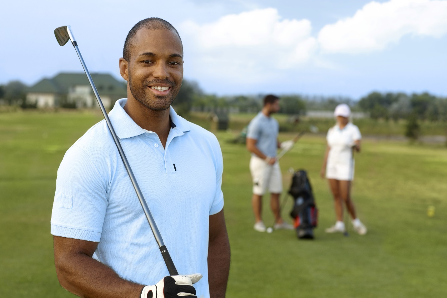 young black golfer with golf club, smiling