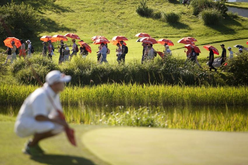People in a golf field with red and white umbrellas