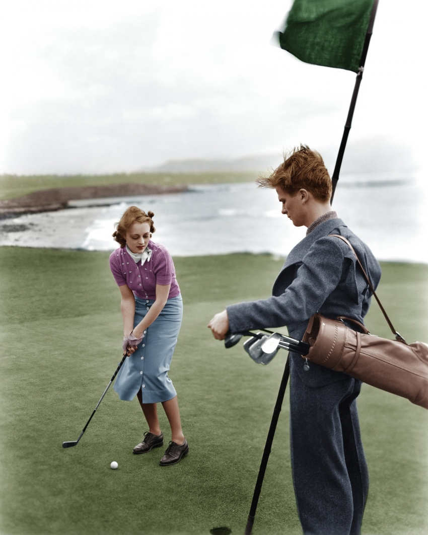 A old picture of a female golfer and a caddie.