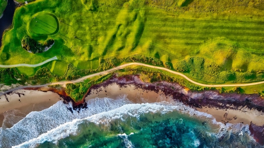 bird's eye view of golf course by the beach
