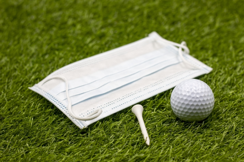 face mask for golfer on green grass