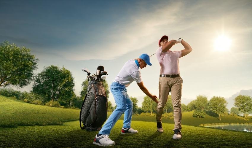 golf instructor adjusting mans golfing stance
