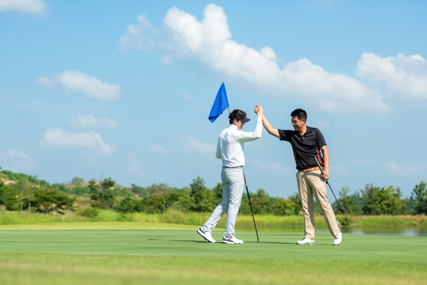 Golfer asian man shake hand for friendship after finish put ball on green.
