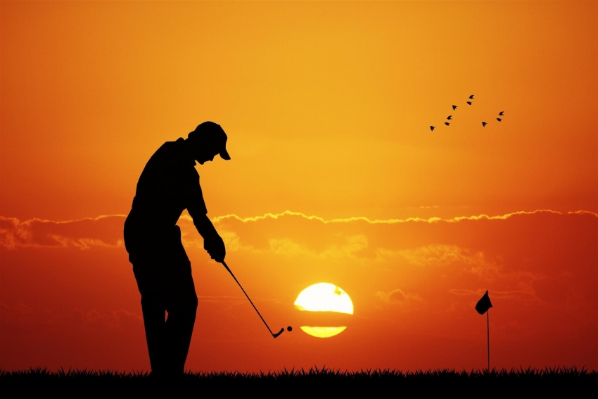 Golfer hitting iron at sunset