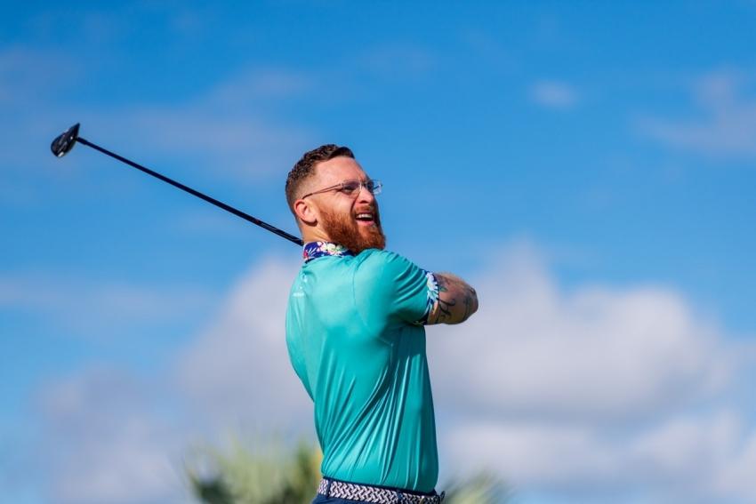 man after swinging golf club