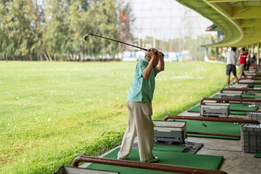 old man swinging club at golf ball at driving range