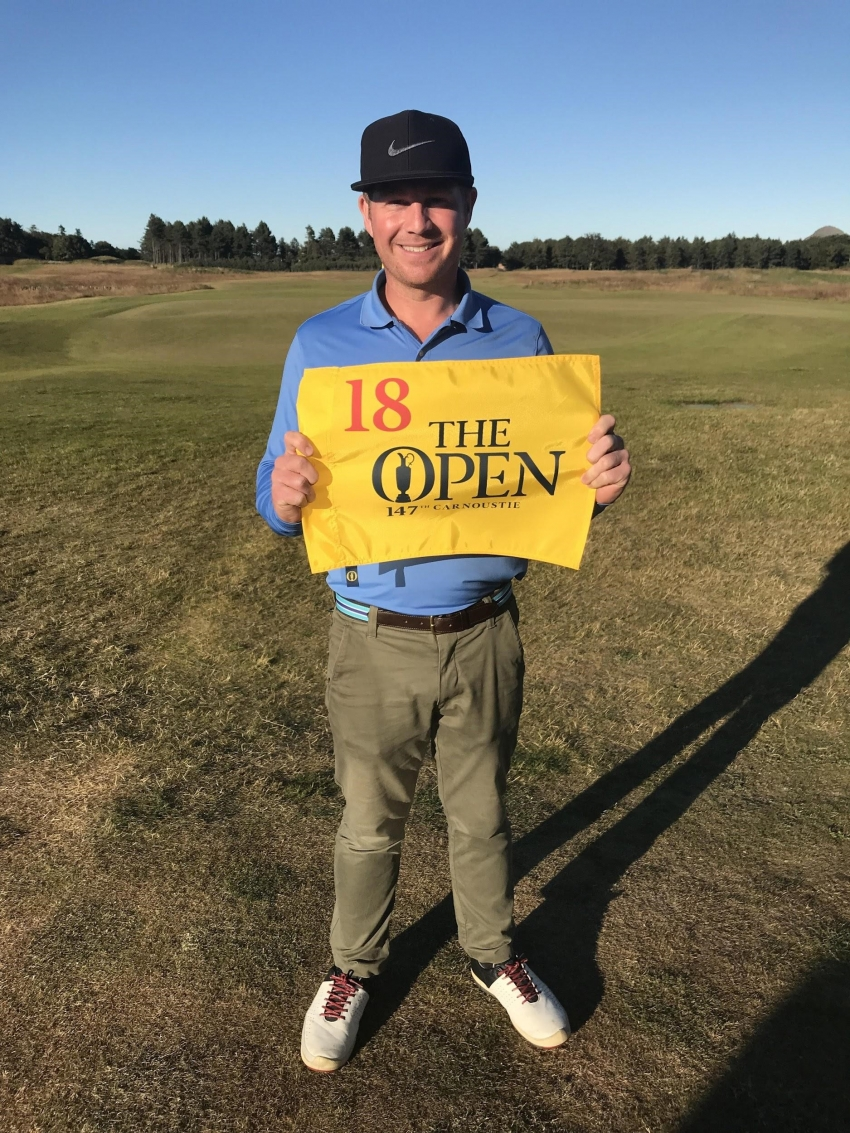 Thomas Curtis holding the banner for the 2018 Open Championship.