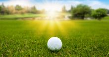 golf ball on green grass with sunrise sunset